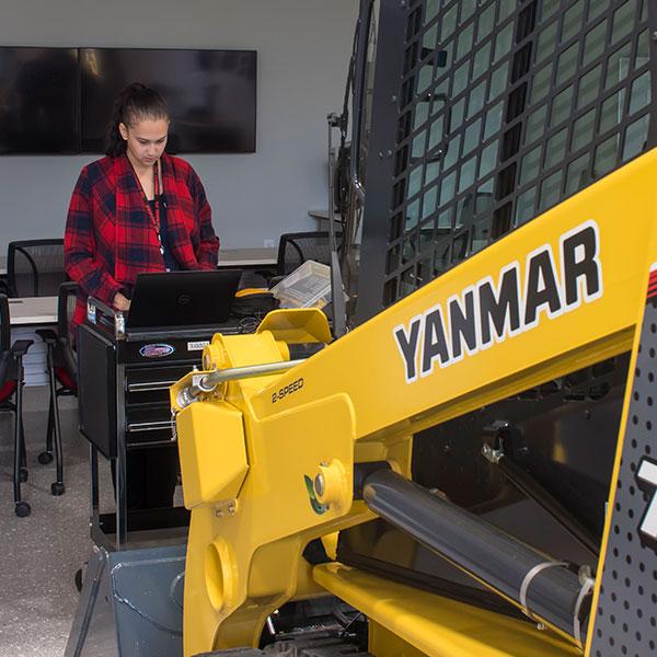 female working on programming a YANMAR skid steer